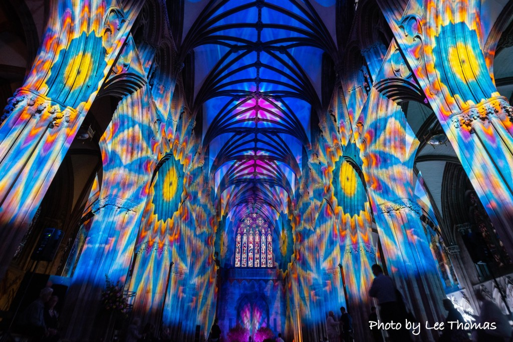 "Lichfield Cathedral, Lichfield, Staffordshire, UK. 16th August 2018. Hundreds of invited guests watch as Lichfield Cathedral is spectacularly lit up to commemorate the centenary of the Armistice. ""The Great Exhibition: Imagine Peace"" is a profound and reflective light and sound installation from the Cathedral's Artist-in-residence Peter Walker, alongside the award winning team Luxmuralis, which is displayed both inside and outside the Staffordshire Cathedral, taking visitors through a series of immersive artworks. Included is the 'Peace Woodland' that creates a labyrinth of exploration as visitors enter The Great Exhibition, walking through 1,918 recently installed trees which envelop the Cathedral grounds throughout the exhibition. The ""Peace Woodland"", a living artwork (again created by Peter Walker in partnership with Lichfield Cathedral and Lichfield District Council), references the end of WWI, the regrowth of the woodlands of the Somme and the Western Front, and the fact that out of conflict, hope returned. Once through the ""Peace Woodland"" the journey for spectators continues inside the Cathedral as the interior is transformed through a vivid series of light and sound installations, as nature is seen to grow over the architecture, a projection of 16 million falling leaves - one for every life lost in WW1, the Sistine Chapel recreated on the Cathedral ceiling as it opens to reveal the sky and psychedelic patterns. Mr Walker, who is in his third year of a five year residency with Lichfield Cathedral, is quoted as saying: ""Imagine Peace offers the visitor the opportunity to say goodbye and honour all those who played their part in the Great War, those who lost their lives, and those supporting them on the home front. Both artistically and emotionally this exhibition is about putting ourselves into the story and taking a moment to think what that means. I want us to walk in the footsteps of the soldiers, I want us to think about peace, I want us"